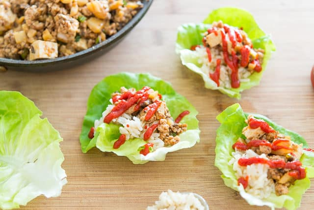 Asian Turkey Lettuce Wraps on a Wooden Board with Sriracha On Top