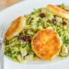 Brussel Sprout Salad Served Warm on White Platter with Dried Cranberries, Almonds, and Crispy Goat Cheese
