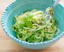 spiralized zucchini oodles in an Italian blue bowl with a fork spinning zoodles coated in basil, olive oil, and parmesan
