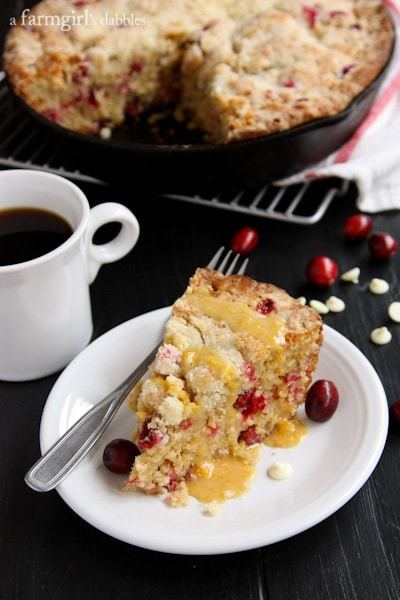 A Slice of Cranberry Orange Skillet Cake on a White Plate with Coffee