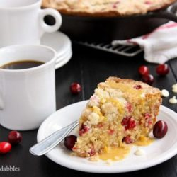 A slice of orange cranberry cake and a cup of coffee