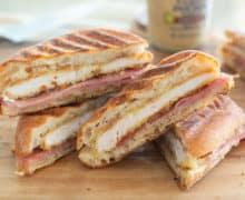 Chicken Cordon Bleu Sandwich - Cut In Half to Show Crispy Chicken Filling on Cutting Board