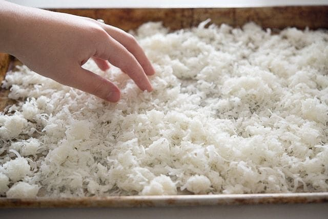 Spreading Sweetened Coconut Flakes on Sheet Pan
