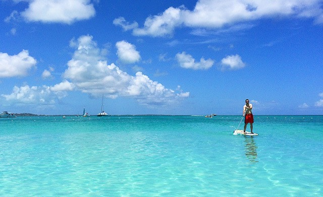 A man doing stand up paddle in the water of Turks and caicos