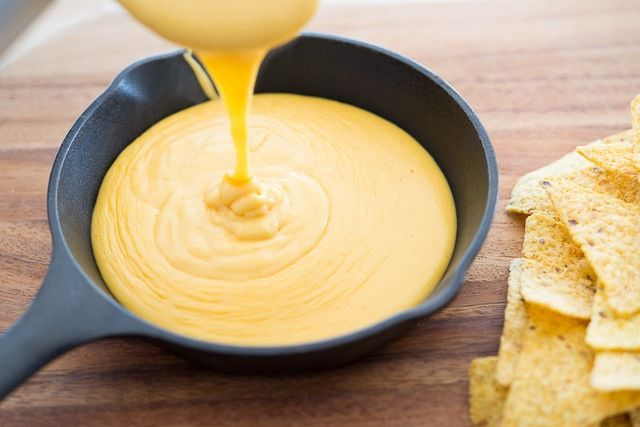 Pouring the Homemade Nacho Cheese Sauce into Cast Iron Skillet