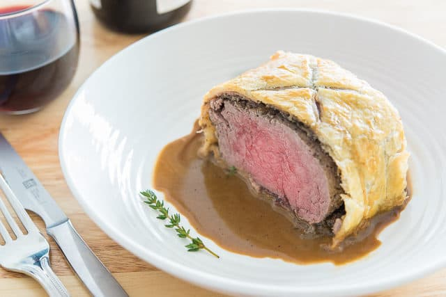 A Piece of Beef Wellington sitting on Pan Sauce
