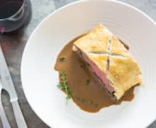 Overhead View of Beef Wellington Sliced and Plated in White Bowl with Pan Sauce