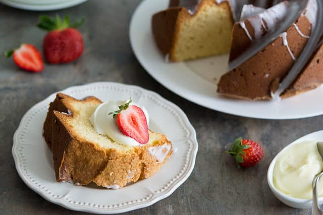 Cream Cheese Pound Cake Recipe - With One Slice on White Plate and Remaining Batch on Plate in Background