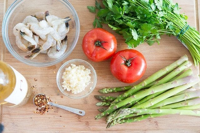 Tomatoes, Asparagus, Shrimp, Herbs, Garlic, and Red Pepper on Cutting Board
