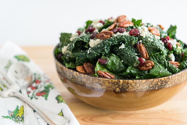 Kale Salad with Cranberries - In a big Brown Ceramic Bowl with Tea Towel Next To It