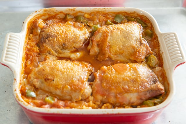 Best Arroz Con Pollo Recipe - Chicken Thighs and Rice Served in a Red Square Baking Dish