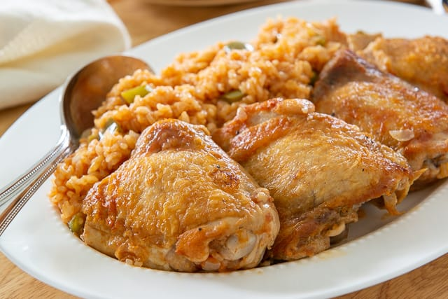 Chicken Thighs On White Platter with Arroz and Spoon