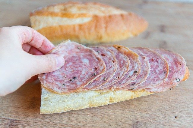 Adding sliced Soppressata Onto Bread