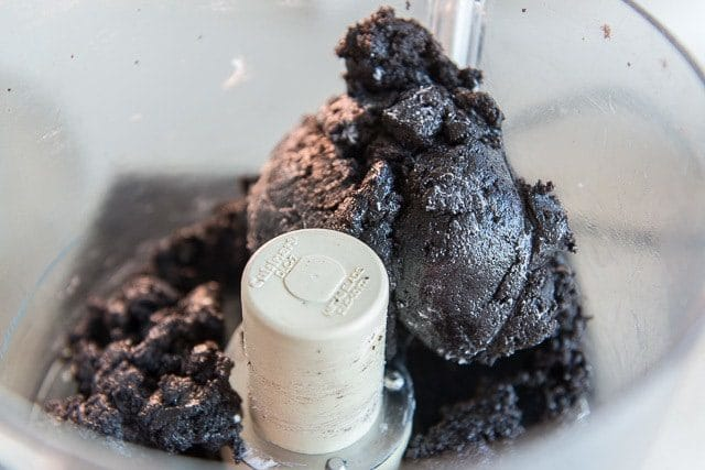 ground up oreo cookies and cream cheese in a food processor bowl in a big clump