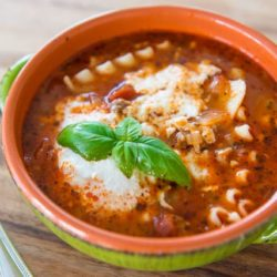 Lasagna Soup In Green Bowl with Basil garnish and Ricotta On Top