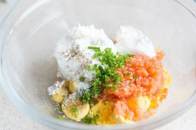 Hardboiled yolks, goat cheese chevre, lemon, chopped smoked salmon, chives, salt, and pepper in a mixing bowl