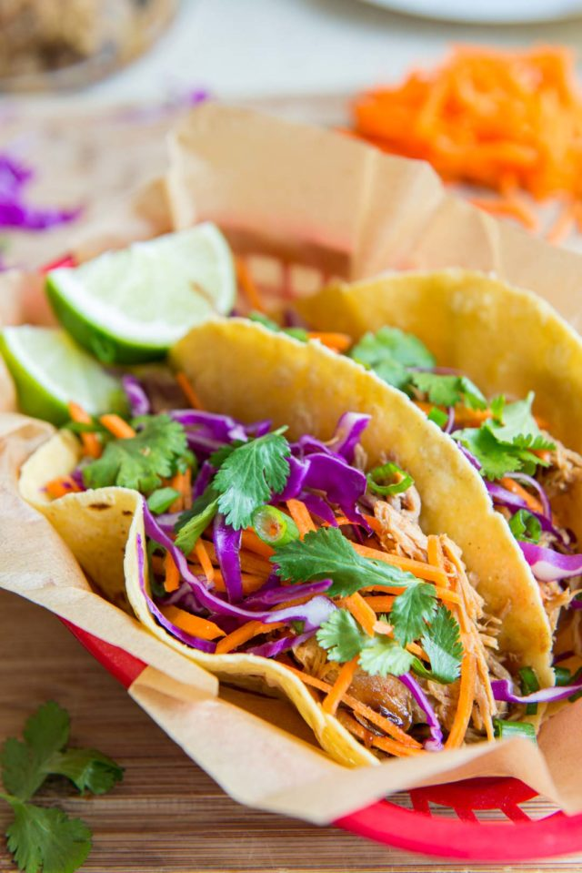 Asian Pork Tacos - in Red Basket After Being Slow Cooker Prepared with Asian Flavors and Lime Wedges