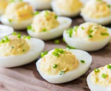 Closeup of rows of deviled eggs with smoked salmon and chives sprinkled on top
