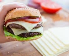 Homemade Double Patty Burger Held by Hand to Show Filling
