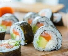 Sushi Recipe - Sliced to See Filling Of Avocado, Salmon, and Cream Cheese on Wooden Board