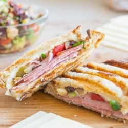 Muffuletta Panini Sandwich On a Wooden board with Cheese