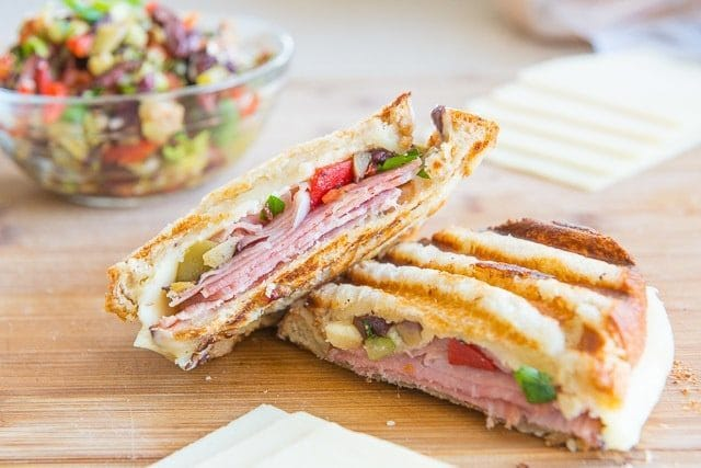 Muffuletta Panini Sandwich - On a Wooden board with Cheese