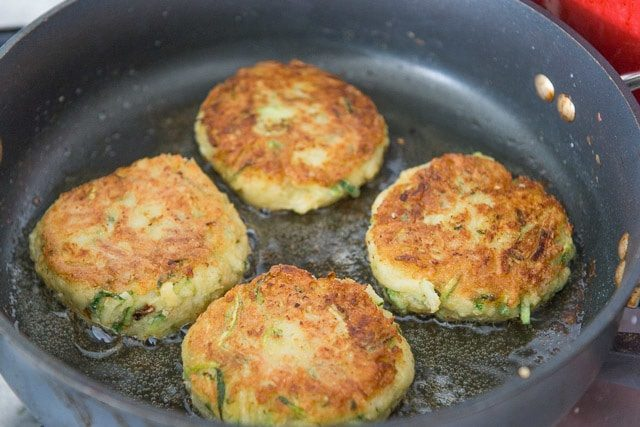 Golden Brown Zucchini Chickpea Fritters in Oil in Skillet