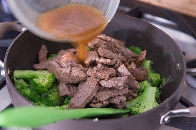 Pouring the Sauce Over the Beef Strips and Blanched Broccoli Florets