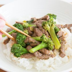 Beef and Broccoli over a Bed Of Steamed White Rice with Chopsticks Picking Up a Piece