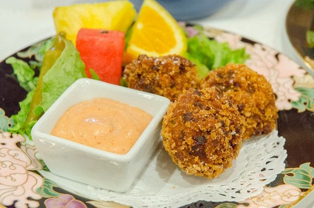 A close up of a plate of food with fritters