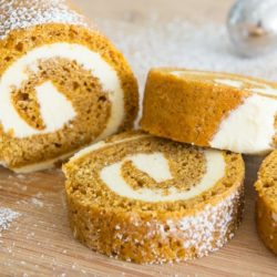 Pumpkin Roll On a Wooden Board with Partial Loaf and Slices