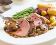 Roasted Beef Tenderloin Slices on Platter with Mushroom Pan Sauce Spooned Over