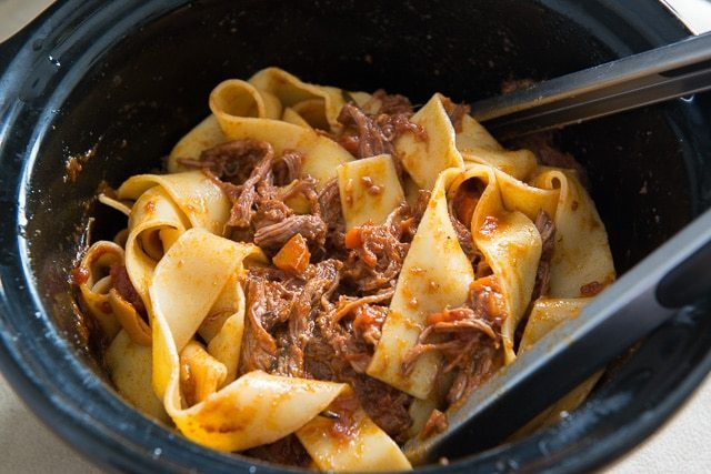 Beef Ragu Pappardelle in a crockpot with Tongs