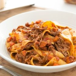 Slow Cooker Beef Ragu Over Pappardelle Noodles in White Bowl