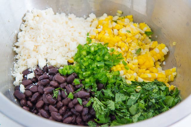 Cotija Cheese, Black Beans, Corn, Green onion, and Cilantro in Mixing Bowl