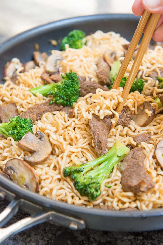 Ramen noodles in a large Calphalon nonstick skillet stir fried with broccoli florets, sliced baby bella mushrooms, with chopsticks digging in to the noodles