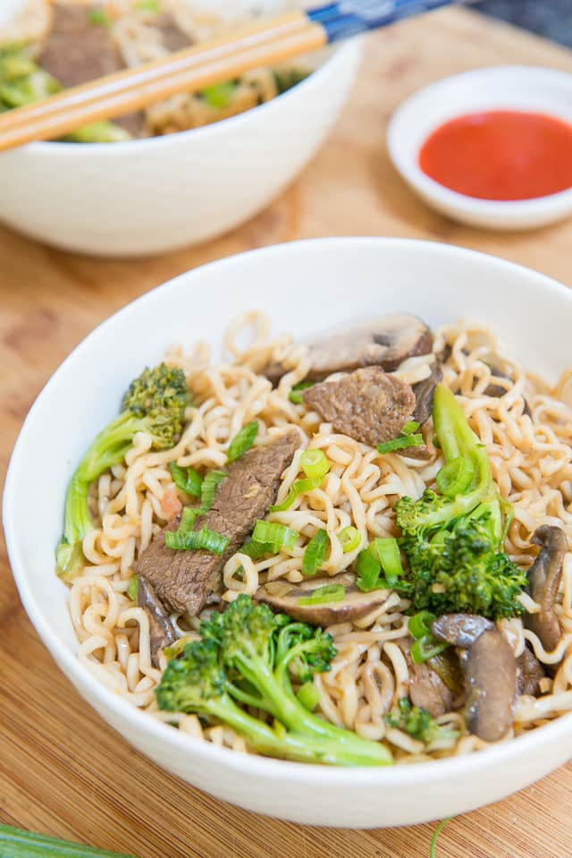 A white Mikasa porcelain bowl with Korean ramen noodles, broccoli, and beef, garnished with scallions, and a side of extra gochujang pepper paste