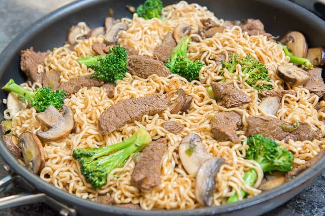 Cooked ramen noodles with broccoli florets, sliced mushrooms, and thinly sliced Korena beef in a Calphalon nonstick skillet