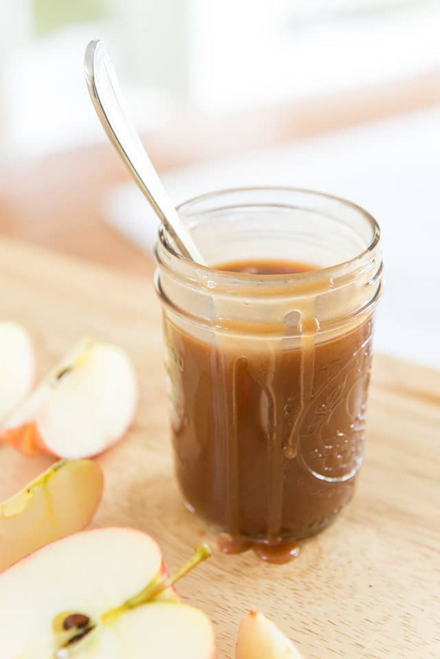 A Mason Jar Of Homemade Caramel Sauce with a Metal Spoon and Sliced Gala Apples On A Wooden Board