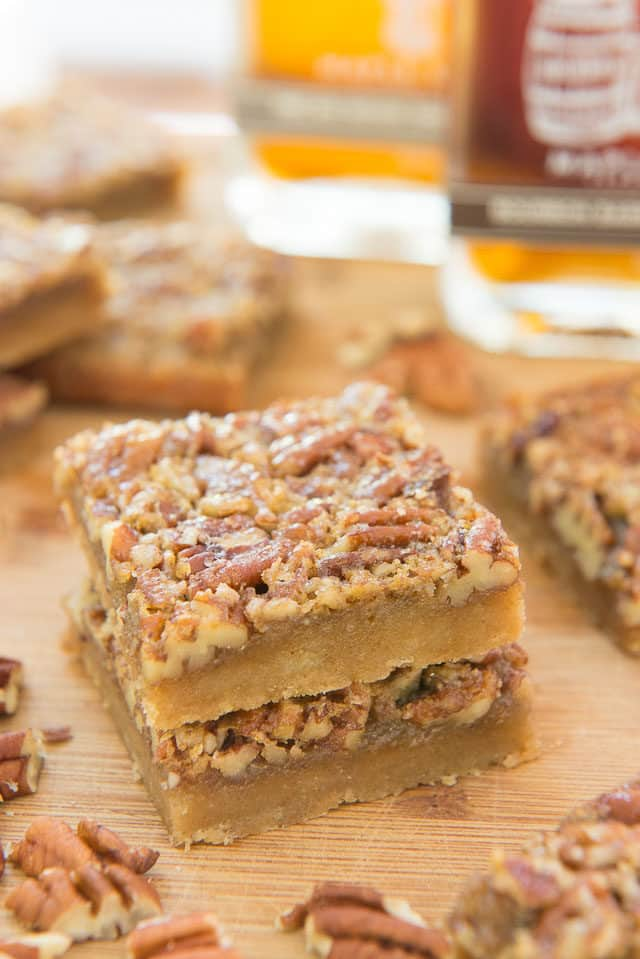 Two Maple Pecan Bars Stacked On Top Of Each Other Surrounded By More Maple Pecan Bars, Two Runamok Maple Syrup Bottles, and Chopped Pecans