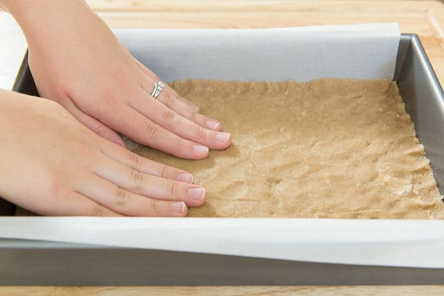9x13 Metal Cake Pan With Parchment Paper Lining And Pressing Out Shortbread Crust
