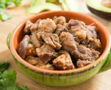 The Best And Simplest Pork Carnitas Chunks In A Green And Orange Bowl With Cilantro And Avocado On Wooden Cutting Board