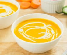 Creamy Blended Carrot Coconut Soup In Mikasa White Porcelain Bowl With Coconut Cream Swirl On Top