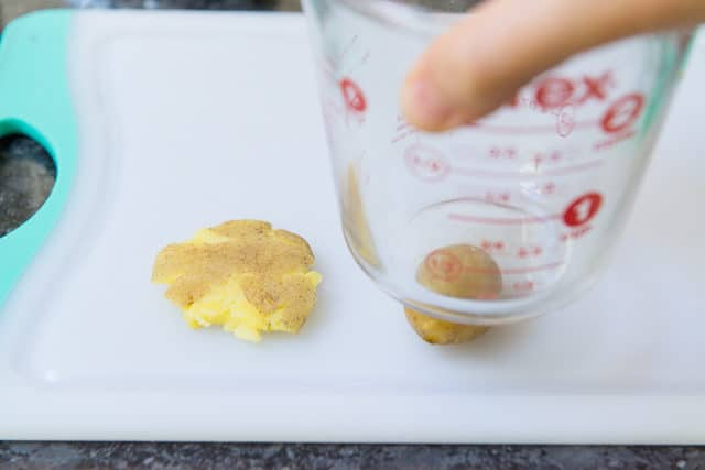 Smashing Baby Potatoes With Pyrex Glass 2-cup Measuring Cup On Poly Board
