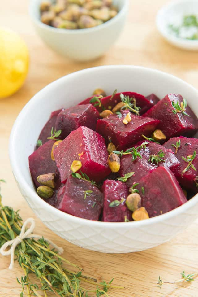 Roasted Beets With Lemon Juice, Olive Oil, Pistachios, And Thyme In A West Elm Ceramic Bowl With A Twine-tied Bundle Of Fresh Thyme Next To It