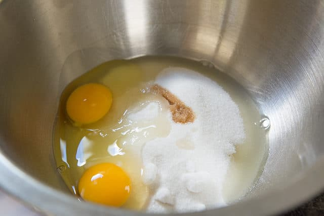 Granulated white sugar, two large eggs, and vanilla extra in a stainless steel mixing bowl