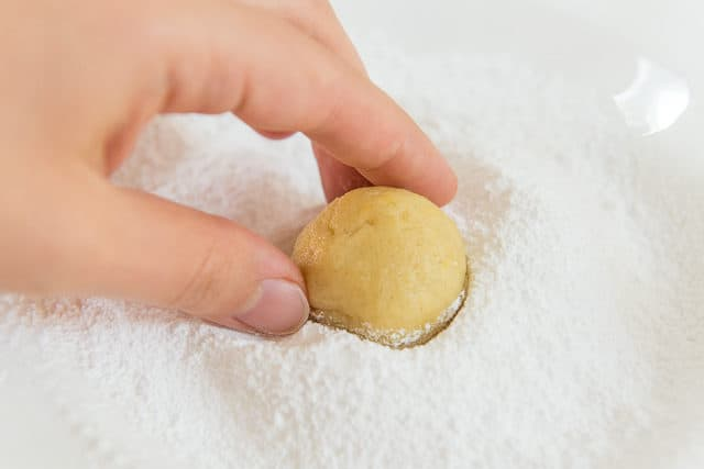 Dipping Lemon Crinkle Cookie Dough Ball Into Sifted Powdered Sugar