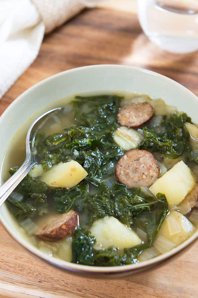 Smoky Andouille Sausage, Kale, and Yukon Gold Potato Soup in Mint Green Bowl and Stainless Steel Spoon