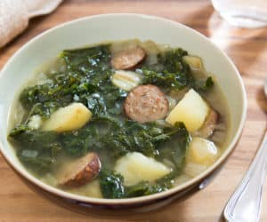 Yukon Gold Potato, Kale, and Andouille Sausage Soup in Brown Ceramic Bowl with Stainless Steel Reed & Barton Spoon and Napkin
