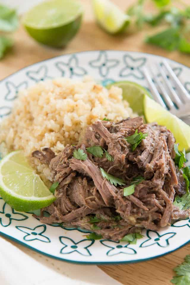 Shredded Indian Style Beef From Natalie Perry's Cookbook With Cauliflower Rice, Chopped Cilantro, And Fresh Lime Wedges On Blue Flowered Anthropologie Plate